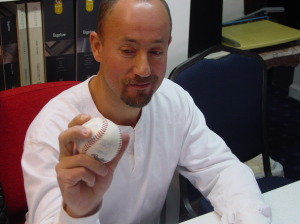 Alatheia client holds a baseball with his thumb prosthesis